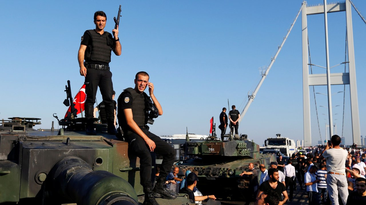 Policemen stand atop military armored vehicles after troops involved in the coup surrendered on the Bosphorus Bridge in Istanbul on July 16, 2016.