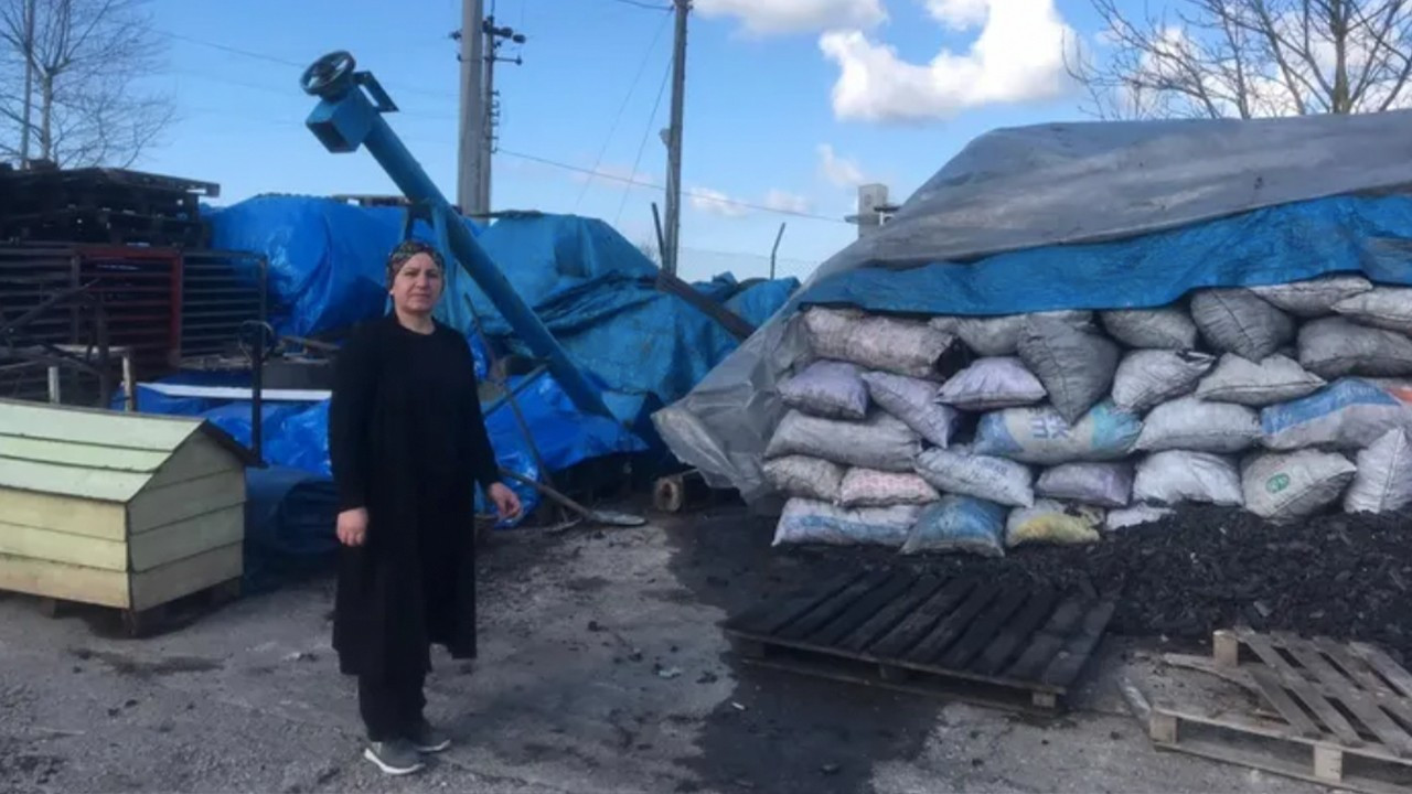 Displaced female entrepreneur piles up equipment on street in protest