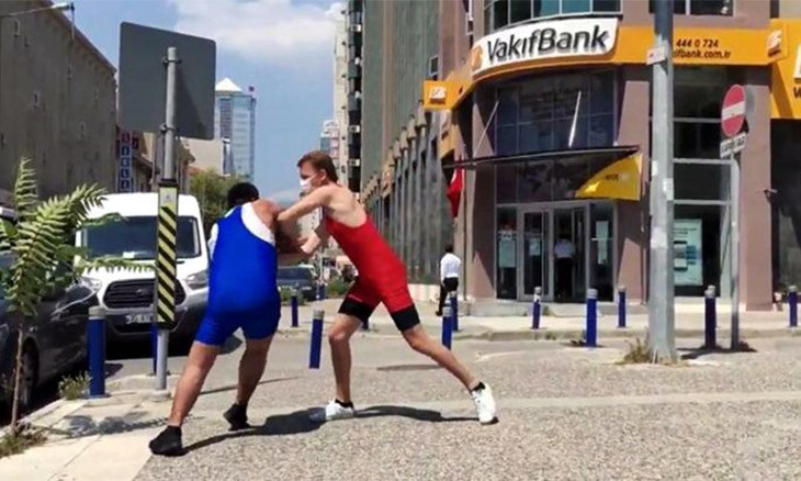 Members of liberal party  wrestle in front of public bank to protest Turkish athlete's board chair