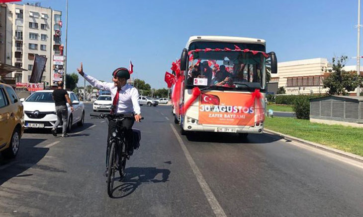 İzmir Mayor tours city on bike when barred from riding parade bus by governor